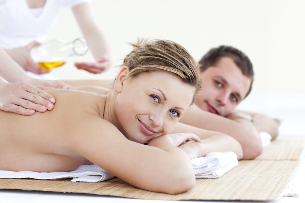 Positive young couple receiving a back massage with oil